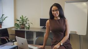 Attractive african american businesswoman smiling in startup office. Young woman in glasses sitting on table with laptop computer on and looking to camera stock footage