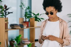 Attractive african american businesswoman in sunglasses using smartphone. In office royalty free stock photos