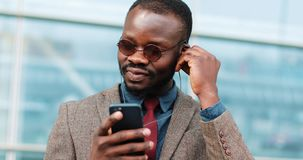 Attractive African American Bussinessman listening to music in headphones standing near office cente in the street. He. Using smartphone in city and dancing to stock footage