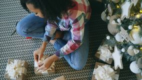 Top view of Attractive mixed race girl packing gift box near Christmas tree at home stock photos