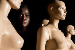 Attractive african american girl standing between dummies and looking at camera. On black royalty free stock photography