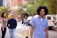 Attractive African American male in a City Street. Four people on city street with young male as focus. Horizontally framed shot Stock Images