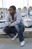Attractive African American male model portrait squatting down a. African American male model portrait squatting down at a boat marina Royalty Free Stock Photos