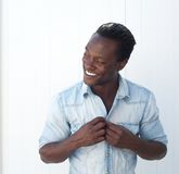 Attractive african american man adjusting shirt button outdoors. Closeup portrait of an attractive african american man adjusting shirt button outdoors royalty free stock image