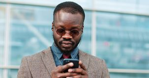 Attractive African American Man using smartphone in city. Handsome young businessman listens to music through headphones. Smiling happy. He standing near office stock video footage
