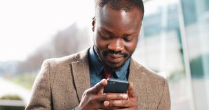 Attractive African American Man using smartphone in city. Handsome young businessman sms texting using app smiling happy. He standing near office cente in the stock video footage