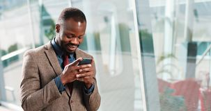 Attractive African American Man using smartphone in city. Handsome young businessman sms texting using app smiling happy. He standing near office cente in the stock video