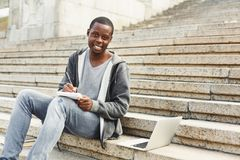 Attractive african-american student making notes sitting on stairs outdoors. Happy attractive african-american student sitting on stairs outdoors making notes Royalty Free Stock Images