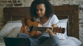 Attractive african american teenager girl concentraing learning to play guitar using laptop computer sitting on bed at