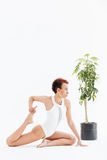 Attractive african american woman doing stretching exercises and practicing yoga Stock Image