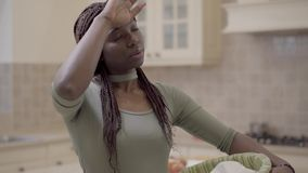 Attractive African American woman with dreadlocks working in the kitchen, she is tired and wipes her forehead with her. Attractive african american woman with stock video
