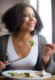 Attractive african american woman eating salad at home Royalty Free Stock Images