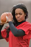 Attractive African American woman football player. Attractive young African American woman in red practice mesh jersey holding a generic American Football Royalty Free Stock Photo