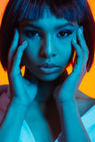 Attractive african american woman with hands on face looking at camera. Portrait of attractive african american woman with hands on face looking at camera royalty free stock image