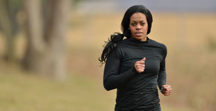 Attractive African American woman jogger runner. Attractive young African American woman in black fitness gear jogging in a park - cold weather Royalty Free Stock Photography