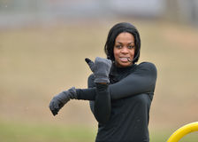 Attractive African American woman jogger runner. Attractive young African American woman in black fitness gear stretching in a park - cold weather Stock Photos