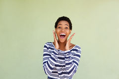 Attractive african american woman laughing against green wall Royalty Free Stock Photos