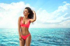 Attractive smiling girl posing on the beach. Attractive african american woman with perfect fit body relaxing on the beach, wearing pink fashionable swimsuit stock images