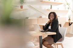 African american woman smiling at camera and sitting in cafe royalty free stock image