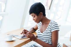Attractive african businesswoman using tablet amd having coffee break Stock Images