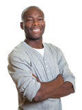 Attractive african man with crossed arms laughing at camera Royalty Free Stock Photos