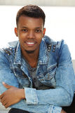 Attractive african man smiling outside in jean jacket. Portrait of attractive african man smiling outside in jeans jacket Stock Photo