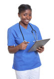 Attractive african nurse working with tablet computer Stock Photography