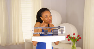 Attractive African woman dancing on scales Stock Images