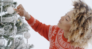 Attractive African woman decorating an Xmas tree Royalty Free Stock Photography