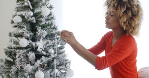 Attractive African woman decorating the Xmas tree Stock Image