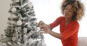 Attractive African woman decorating the Xmas tree Stock Photography