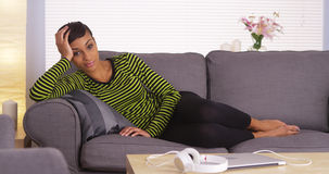 Attractive African woman lying on couch Stock Photography