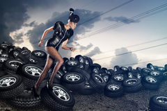 Attractive african woman on tires on the cloudy sky Royalty Free Stock Photography