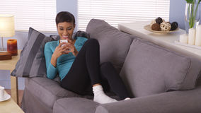 Attractive African woman using smartphone on couch Stock Photo