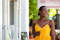 Attractive african woman walking outdoors with flower Stock Photography