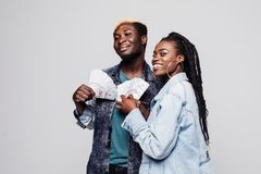 Lottery win cash. Attractive afro american couple with cash dollars in hands looking away isolated on white background. Attractive afro american couple with cash stock photography