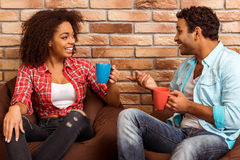 Attractive Afro-American couple. Drinking coffee, talking and laughing while sitting on beanbag chair against brick wall Royalty Free Stock Photography