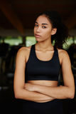 Attractive afro american girl standing in a short tank top is resting after training in the gym Royalty Free Stock Photos