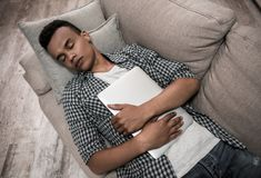 Afro American guy at home. Attractive Afro American guy in casual clothes is hugging a laptop while sleeping on couch at home royalty free stock image