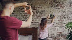 Attractive aian girl is choosing place for picture on brick wall while her husband is making frame shape with his. Fingers and looking at her. Decorating flat stock video footage
