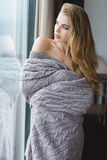 Attractive alluring female in grey coverlet looking through the window Royalty Free Stock Photos