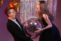 Attractive amazed young couple holding disco ball Royalty Free Stock Photography