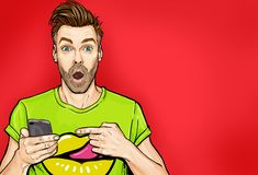Attractive amazed young man pointing finger on mobile phone in comic style. Pop art surprised guy. Holding smartphone vector illustration