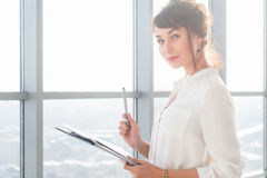 Attractive ambitious businesswoman standing in modern office, holding paper folder, looking at camera, smiling. Attractive ambitious businesswoman standing in stock photo