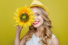 Free Attractive And Awesome Young Woman Is Holding A Sun Flower Close To Her Face. She Is Looking To Camera And Smiling. This Stock Image - 115722831