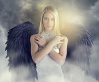 Attractive angel with black wings. Beautiful angel with black wings over a cloudy background stock photos