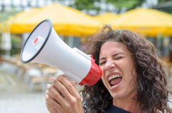 Attractive angry woman shouting into a megaphone Stock Image