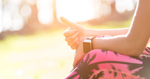 Attractive anonymous sportive woman wearing smart watch showing thumb up after workout session Stock Image