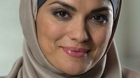 Attractive arab woman in headscarf smiling on camera, perfect make-up, wellness. Stock footage stock video footage