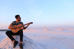 Attractive Arabian guy sings songs on guitar, sitting on hill in Royalty Free Stock Photos